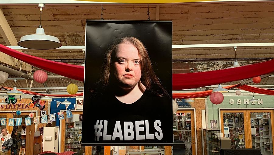 An exhibition photo of a young woman who has Down's Syndrome and is wearing a T-shirt with the word Labels on it. It hangs in a large hall