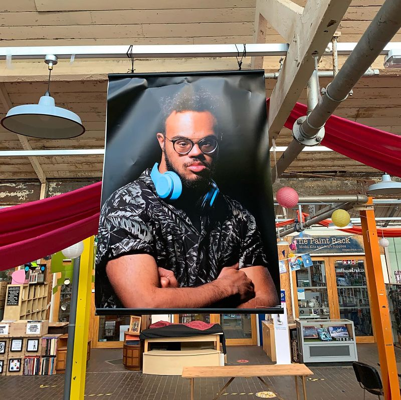A young man with Down's Syndrome wears headphones around his neck in an exhibition image hanging in a large hall