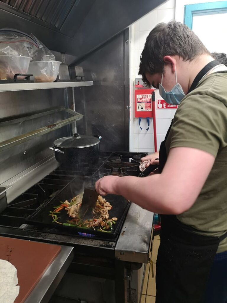 Curtis, a participant of Teenvine Plus, learns to fry chillies in the professional kitchen of a Coventry Mexican restaurant