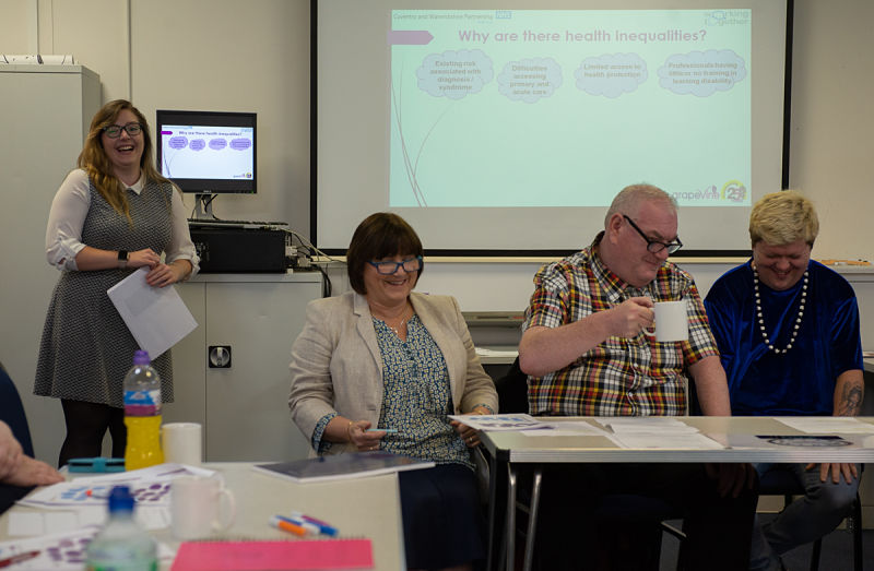 Two women and two men from the Health Team sit in front of a presentation they are delivering to a group of health professionals