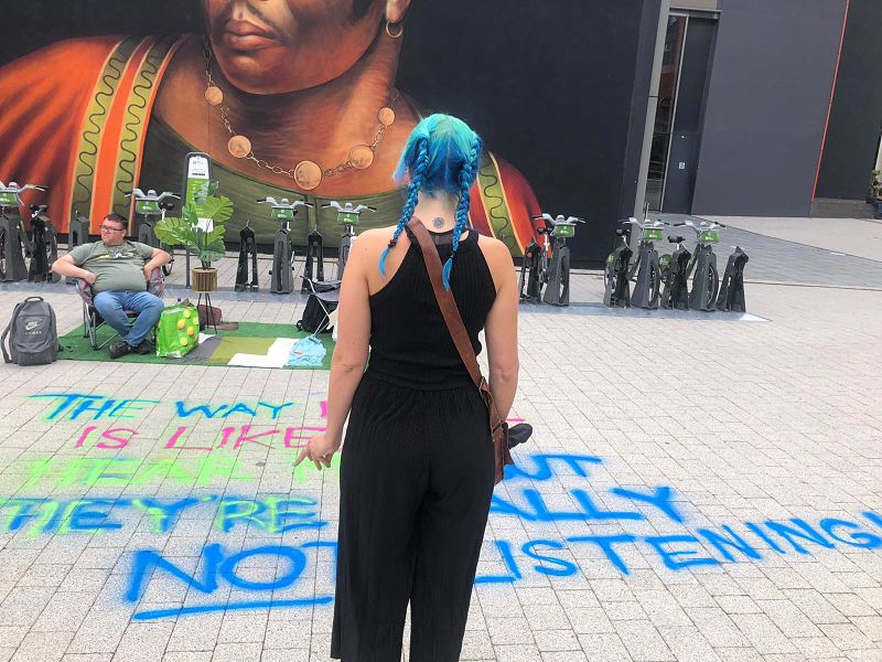 A woman with blue hair in pigtails wearing black looks across a Grapevine parklet in Coventry city centre with faux grass, chairs and graffiti sprayed on the pavement