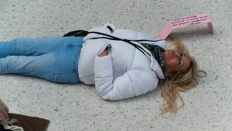 A woman in a white coat lies on the floor in a public space