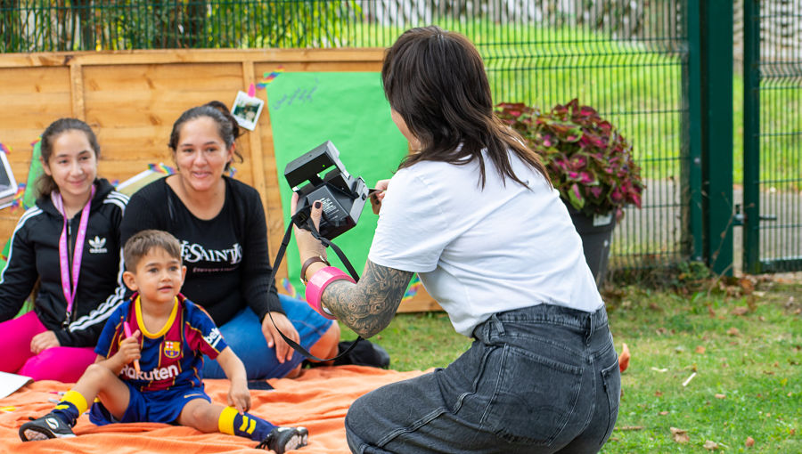A woman in jeans takes a photo of a family at the BBQ using an instant camera