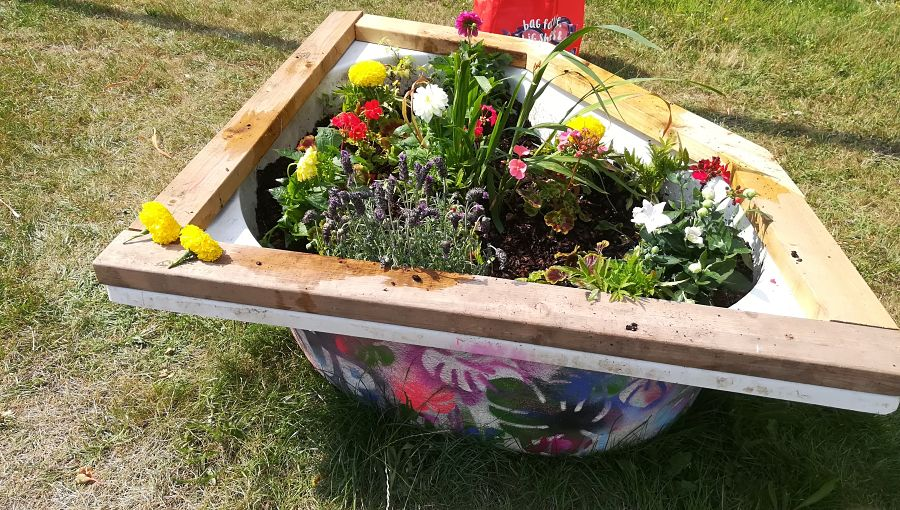 A planted recycled bathtub filled with flowers and decorated with paint