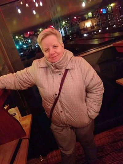 A woman wearing a coat and handbag smiles at the camera in a bar