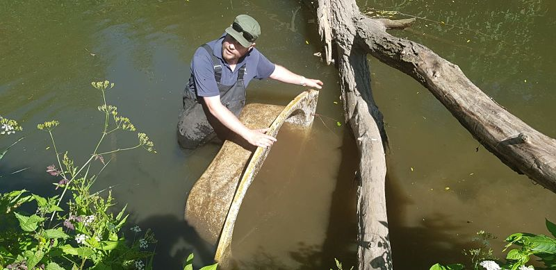 A man in waders pulls a bathtub from the River Sowe in Coventry