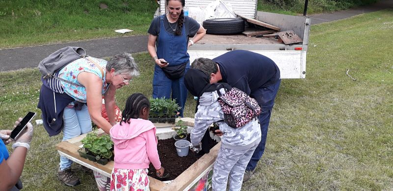 People gather around a recycled bathtub planting it with plants and flowers in Coventry