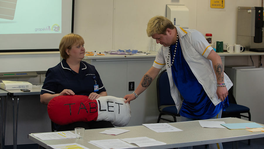A man hands a large pretend pill to a nurse during a demonstration