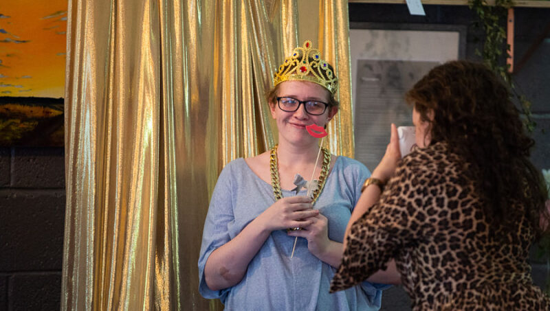 A young woman poses for the camera wearing a dress up crown in front of a gold curtain.