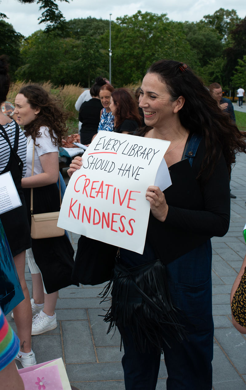 Melissa from the Grapevine team smiles holding a poster about Creative Kindness