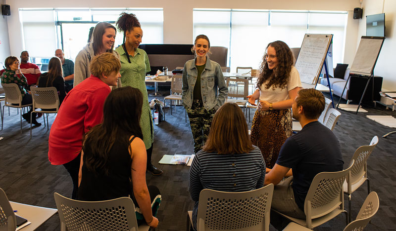Grapevine team members sit and stand in a circle at a team away day
