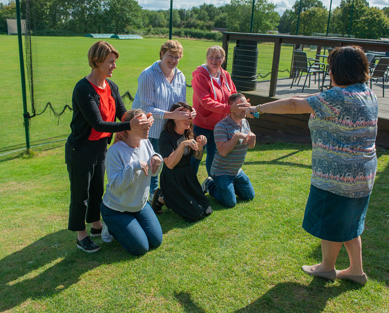 Grapevine team members act out Three Blind Mice at a team away day
