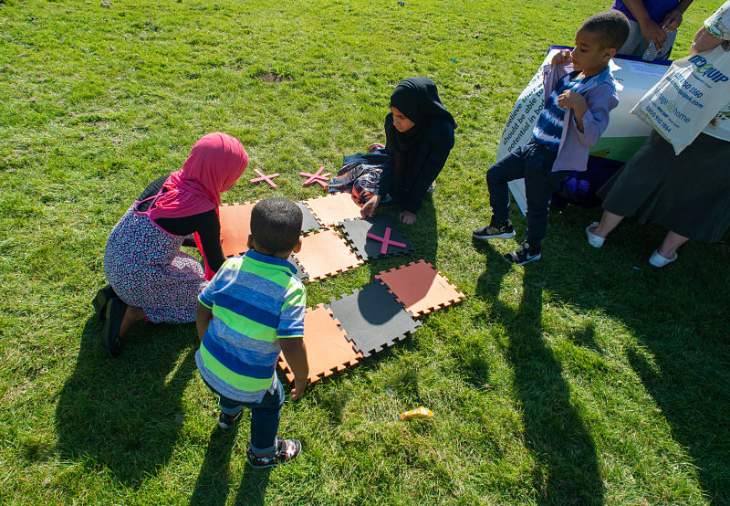 A group of women with children put a large foam mat jigsaw together on grass