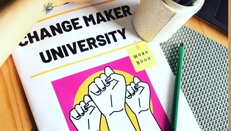 A cup rests on a Changemaker University workbook
