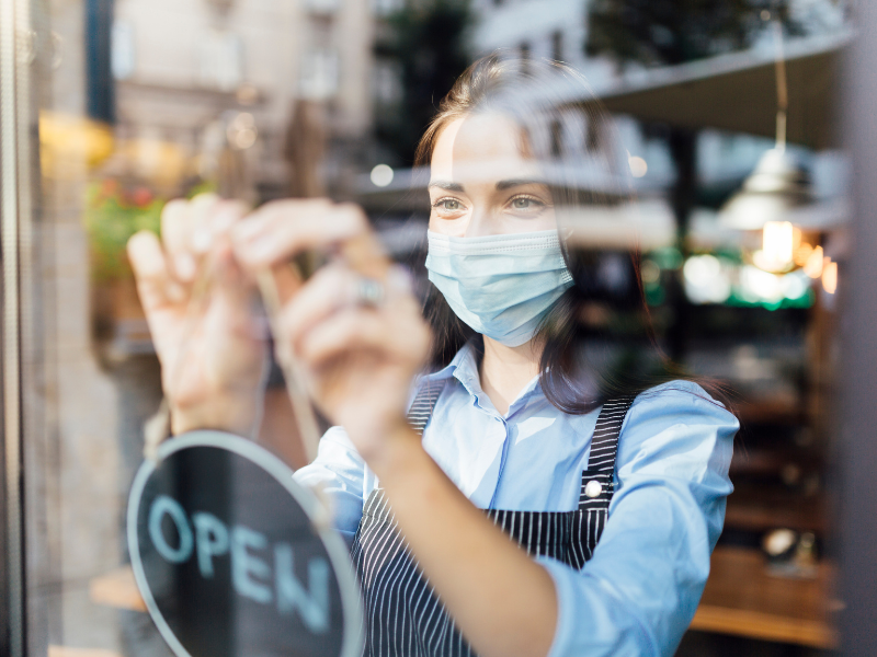 A young woman wearing a face mask hangs an 'Open' sign on the window of a coffee shop