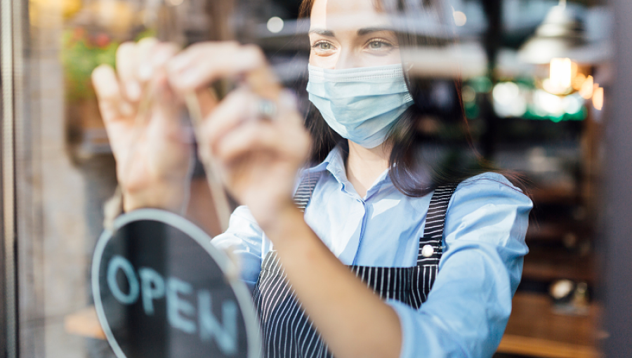 A woman wearing a mask and an apron hangs an Open sign in a shop window