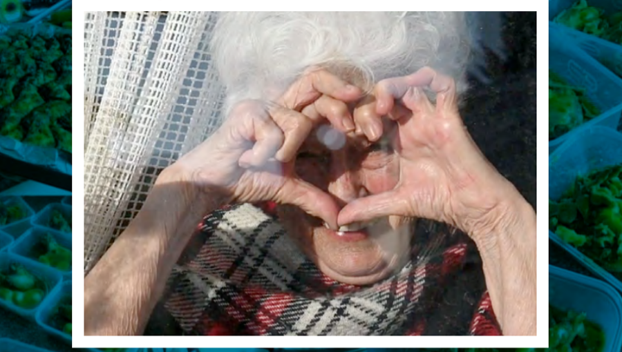 Lady makes heart shape through window during 2020's pandemic