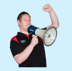 A man raises one hand in a fist and holds a megaphone to his lips with the other