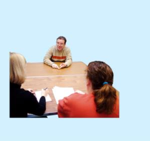 Three people sit around a table talking