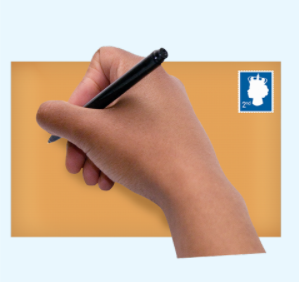 A hand holding a pen writing on a brown envelope with a stamp in the corner