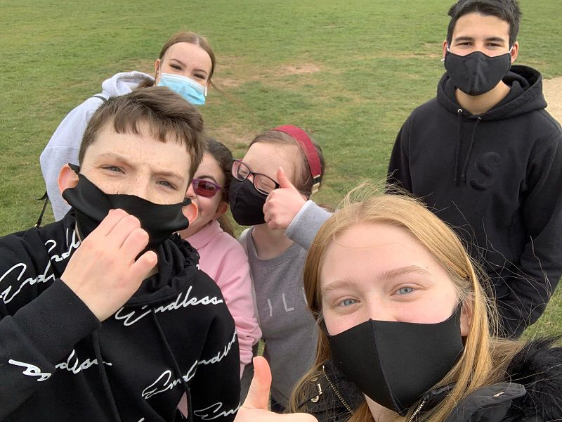 A group of teenagers wearing face masks give the thumbs up to the camera in a Coventry park