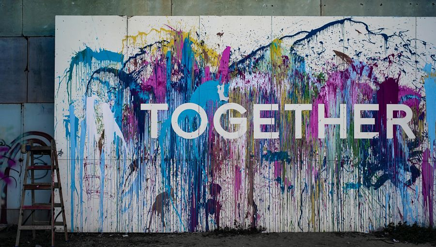 The word Together on a wall amongst splattered coloured paint