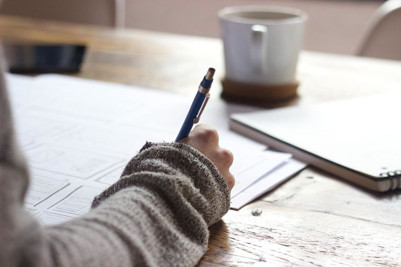 A person writes on paper with a coffee mug on the table