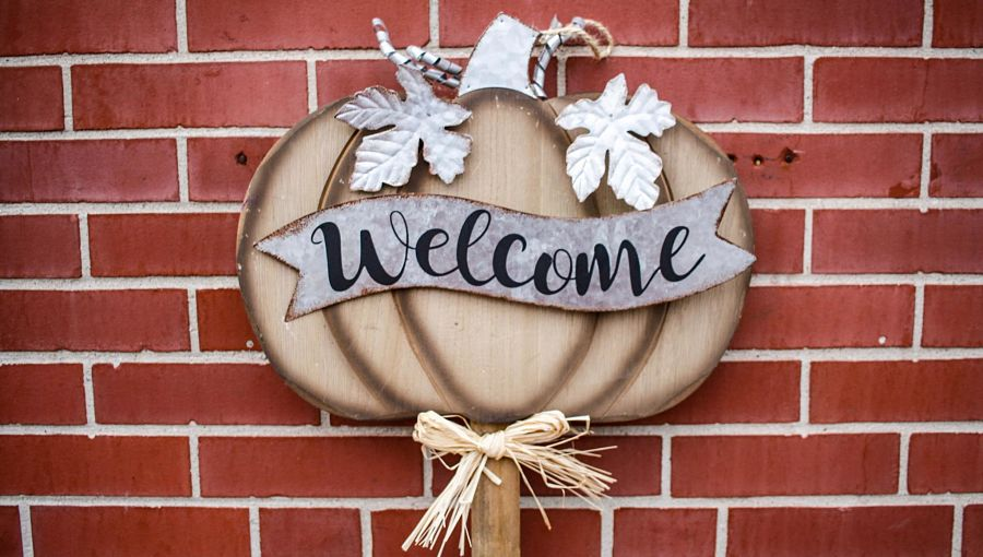 A pumpkin Welcome sign stands against a red brick wall