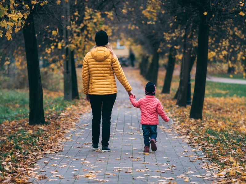 Mum and toddler son take a walk through an autumn park
