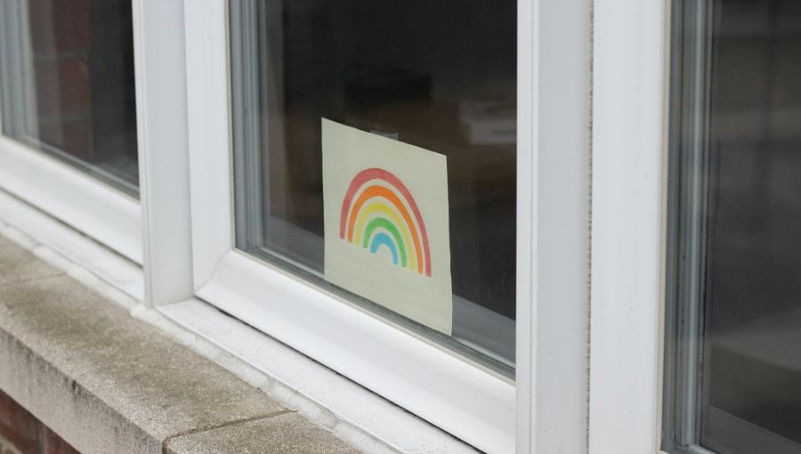 A hand drawn rainbow in a window