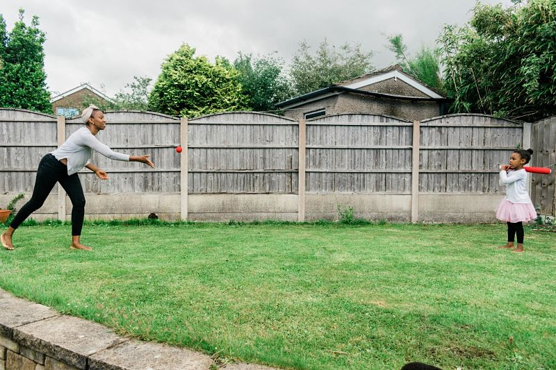 A black woman throws a red ball to a child holding a bat in a back garden on the grass