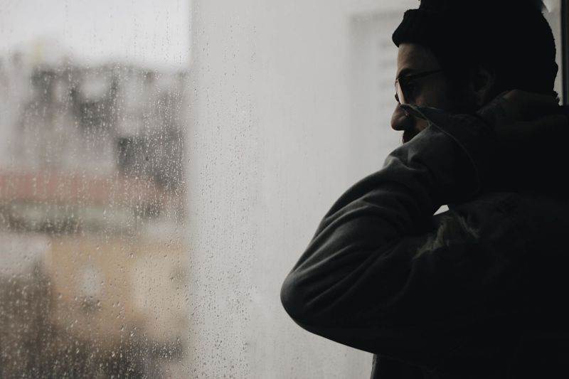 A man in a hat and glasses looks out of a rainy window